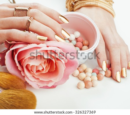 woman hands with golden manicure and many rings holding brushes, makeup artist stuff stylish, pure close up, pink tender rose flower