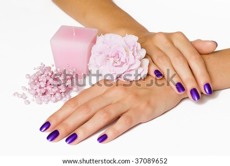 Woman hands with manicure, candle, flower and beads
