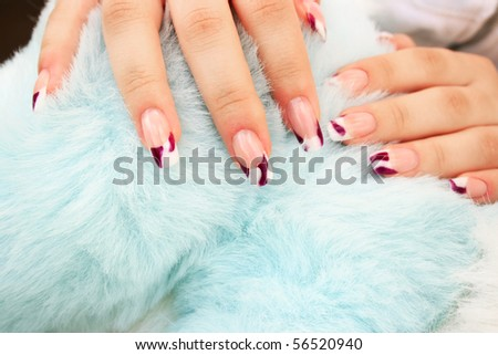 Woman hands with nail art on blue fur background.