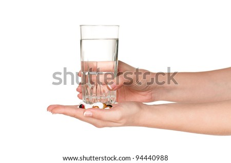 Woman hands with pills and glass of water isolated on white background