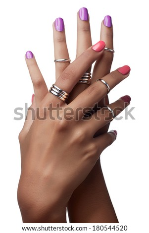 Woman hands with purple and pink nail polish and silver stacking rings on white background