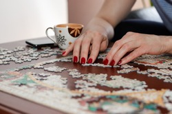 Woman hands with red nail polish putting jigsaw puzzle pieces together. Stay at home concept. Home quarantine. Coronavirus outbreak and family concept.