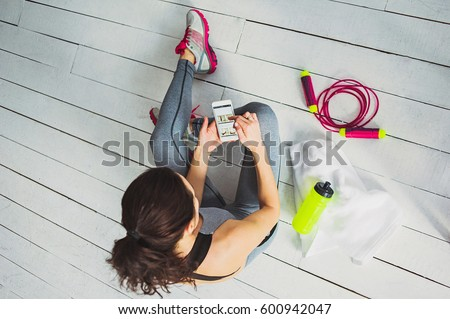Woman hands with touchscreen mobile phone. View from above studio shot on wooden floor background. Fitness and healthy life concept.