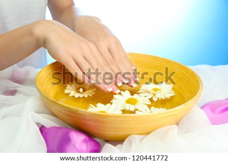 woman hands with wooden bowl of water with flowers, on blue background