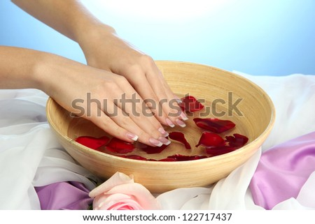 woman hands with wooden bowl of water with petals, on blue background