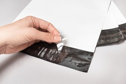 Woman hands working with white polythene envelopes on grey background