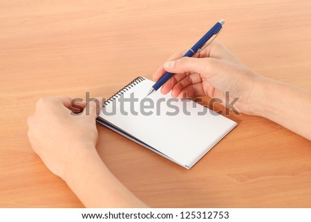 Woman hands writing in a notebook on a table in a white isolated background
