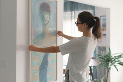 Woman hanging a painting at home and decorating her contemporary living room