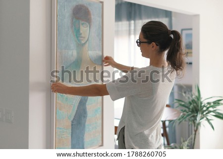 Woman hanging a painting at home and decorating her contemporary living room Foto stock ©