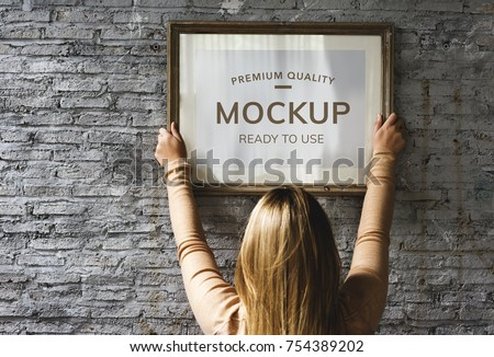 Woman hanging a photo frame mockup