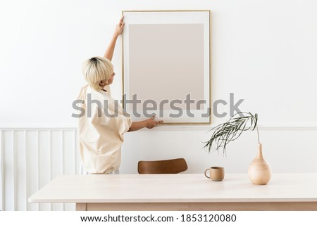 Woman hanging a photo frame on a white wall mockup Stockfoto ©