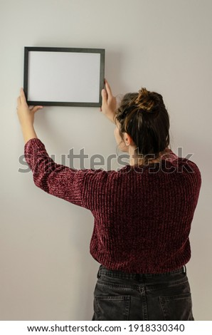 woman hanging black frame with white background Foto stock ©