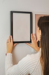 woman hanging black picture frame with white background