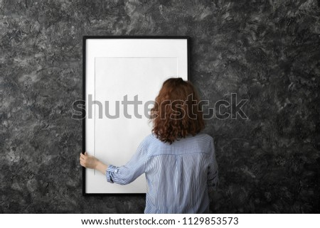 Woman hanging blank photo frame on dark wall