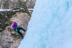 Woman hanging on a rope attached to her harness, climbing down the side of an icy slope