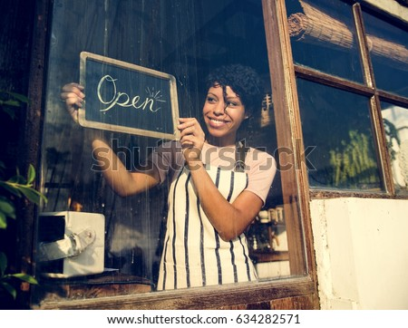 Woman Hanging Open Sign by the Glass Window #634282571