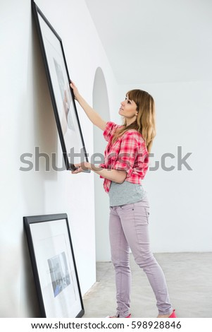 Woman hanging picture frame on wall in new house