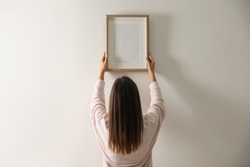 Woman hanging picture on white wall indoors