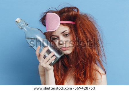woman hangover on a blue background bottle of alcohol morning