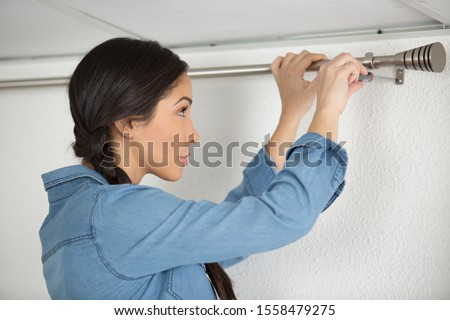 woman hangs up the a curtain indoor s