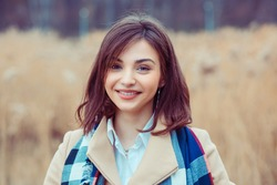 Woman happy. Closeup portrait headshot of beautiful smiling toothy girl student looking at you camera park city site cityscape background. Multicultural mixt race asian russian model Happiness concept