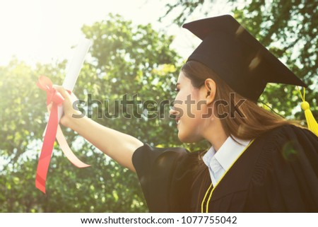 woman happy graduate showing certificated in hand with in the garden.color tone #1077755042