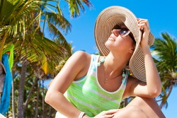 Woman happy in a summer hat under the palm trees. Girl enjoying sun day looking up at sky smiling cheerful.