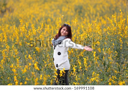 woman happy in free freedom pose with arms raised up towards the sky with smiling cheerful, elated expression of happiness. Beautiful girl in colorful of yellow blossom ,  flower forest outdoor