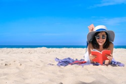 Woman happy smiling and read books on the beach on a beautiful . Pretty girl asian in casual looking away and smile , laughing. The beach beautiful at bright sky