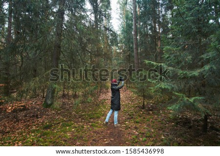 Woman has a walk in autumn forest and making photos on smartphone