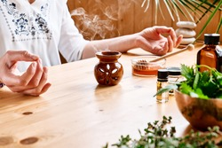 Woman has aromatherapy session at the table with essential oil diffuser medical herbs, different types of oils and essences. Aromatherapy and alternative medicine concept. Natural remedies.