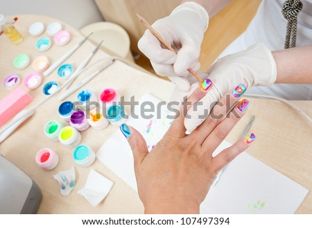 woman have nail coloring treatment in manicure salon