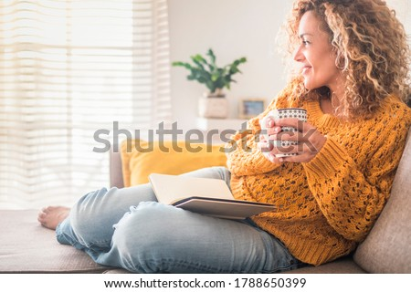 Woman have relax at home with cup of tea and book - reading activity for adult beautiful female people - enjoying quiet lifestyle indoor and long blonde curly hair - happy adult female indoor