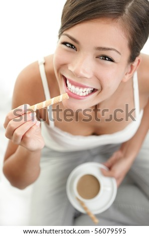 Woman having a coffee break and eating a cookie while smiling.
