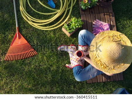 Woman having a coffee break while working in the garden