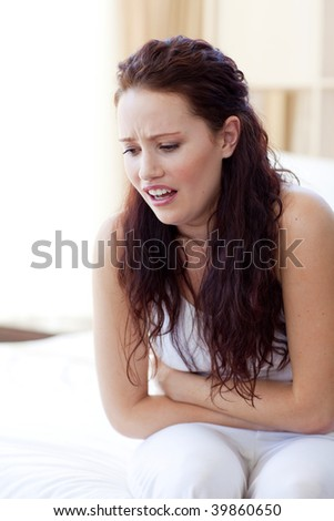 Woman having a stomachache sitting in bed
