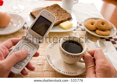 woman having breakfast and holding a spoon and a telephone checking for messages