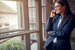 Woman having business conversation on cell phone indoor by window