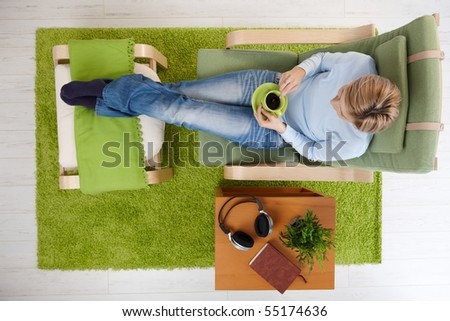 Woman having coffee sitting in armchair with legs crossed on footboard in high angle view.?