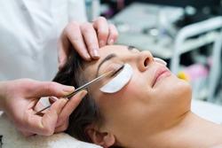 woman having eye lashes tinted in beauty salon