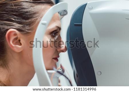 Woman having eyesight test using modern refractometer looking into the machine