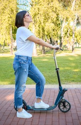 Woman having fun in park. She is riding blue scooter. She is wearing red glasses, white shirt, blue trousers and sneakers. Beautiful sunny day in nature. Outdoor photography.