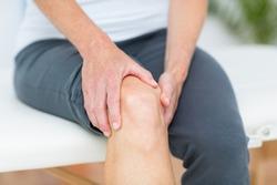Woman having knee pain in medical office
