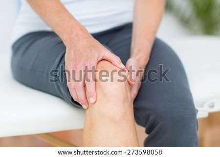 Woman having knee pain in medical office