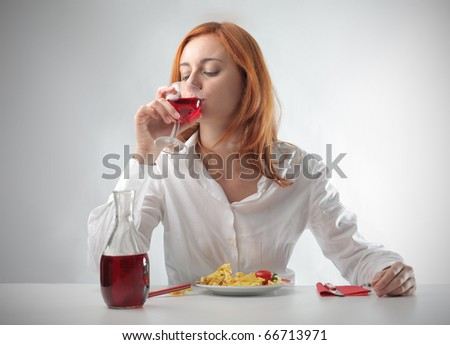 Woman having lunch and drinking a glass of red wine