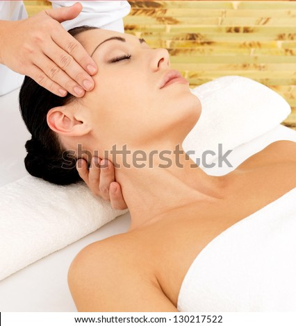 Woman having massage of face in the spa salon. Beauty treatment concept.