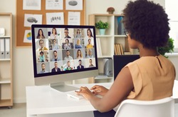 Woman having online business conference or video call staff meeting. Young black lady sitting at office desk with computer talking to team of coworkers who work from home or have hybrid work schedule