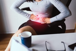 Woman having painful stomach ache during working from home,Female suffering from abdominal pain,Period cramps,Hands squeezing belly,Stomach pain
