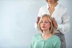 Woman having reiki healing treatment , alternative medicine concept, holistic care. Close Up Of A Relaxed Young Woman Having Reiki Healing Treatment. Alternative medicine and holistic health care.