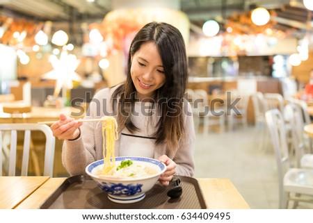 Woman having remen in restaurant
